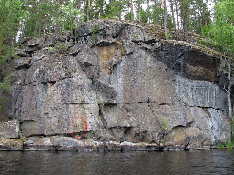 Kalliomaalaus erottuu heikosti pienen kalliokolon yläpuolella. Tässä maalauksen paikka on ympyröity. Maalauksen ihmishahmon alareuna on 77 cm terassin yläpuolella ja 17 cm kalliokolon yläreunasta.