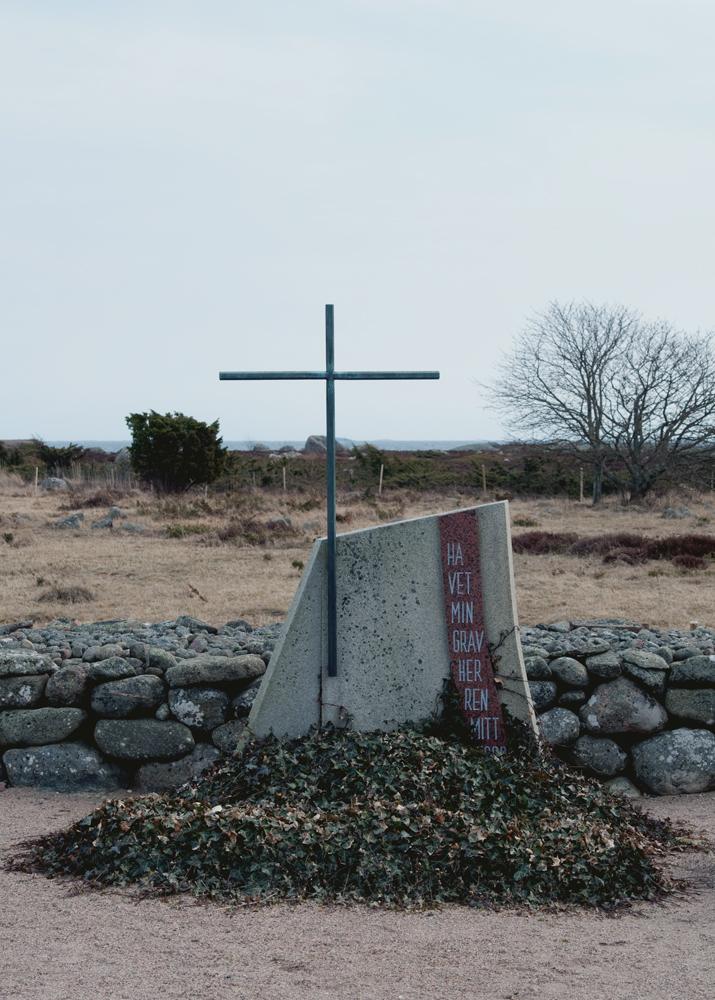 """Utön hautausmaalla on Gösta Bergmanin suunnittelema hukkuneiden muistomerkki. Luotsiveneen purjeen muotoisessa kivessä lukee """"Havet min grav Herren mitt hopp""""."""