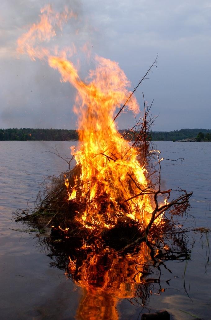 Kuvassa on järveen isoista oksista rakennettu juhannuskokko.