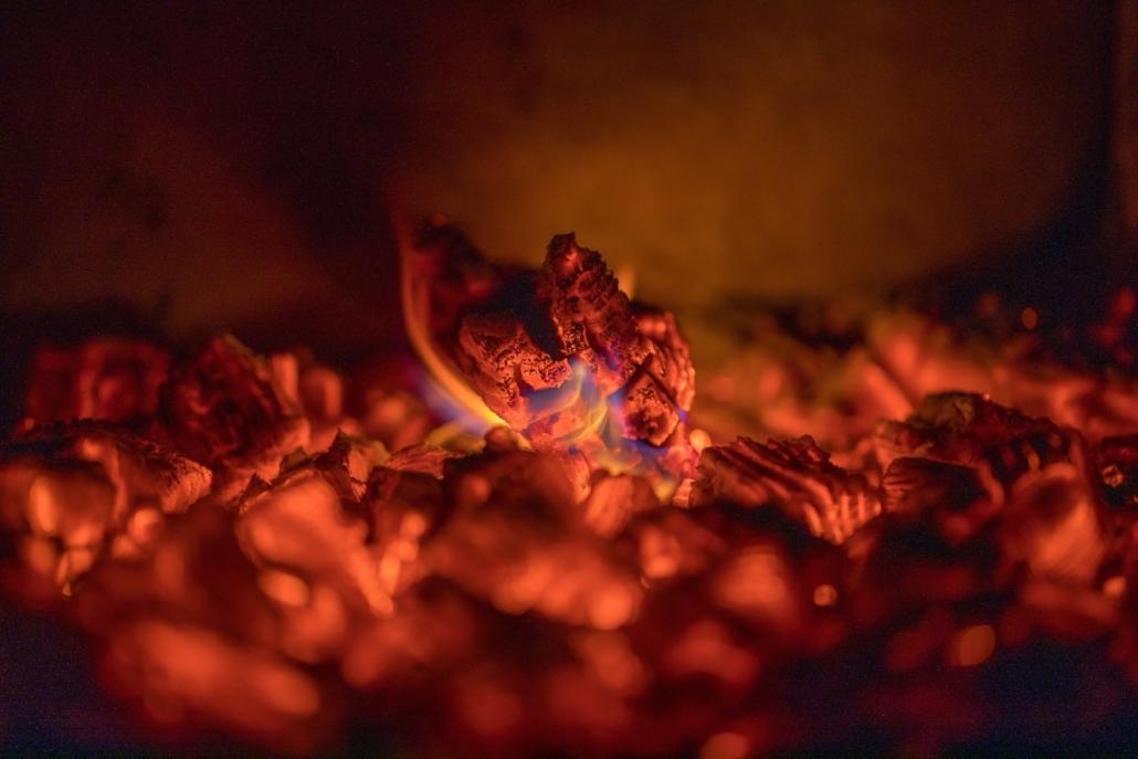 Kuvassa on kuumana hehkuvia hiiliä nuotionpolton jäljiltä.