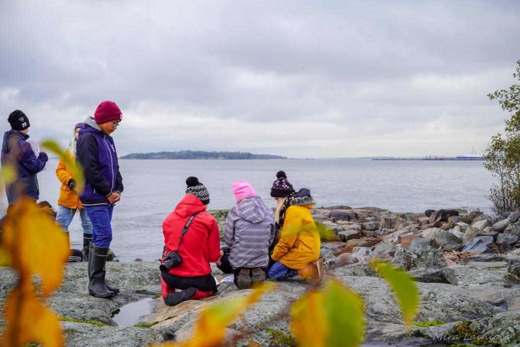 Koululaiset ovat luontokouluopettajan kanssa kalliolla meren rannalla