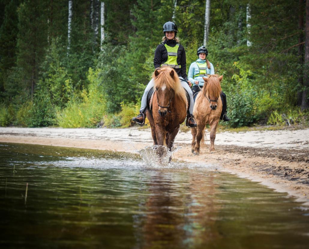 Kaksi hevosta ratsastajineen hiekkarannalla Kuva: Terhi Ilosaari