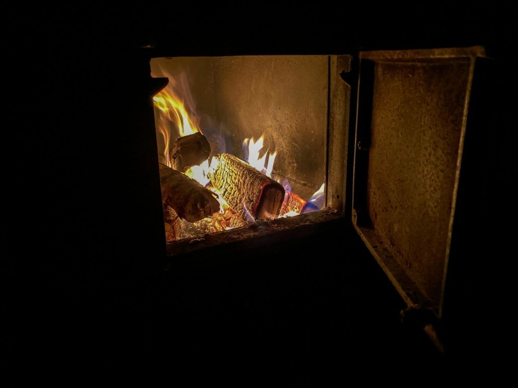 Joulusaunan kiukaan avoin luukku ja palavat puut.
