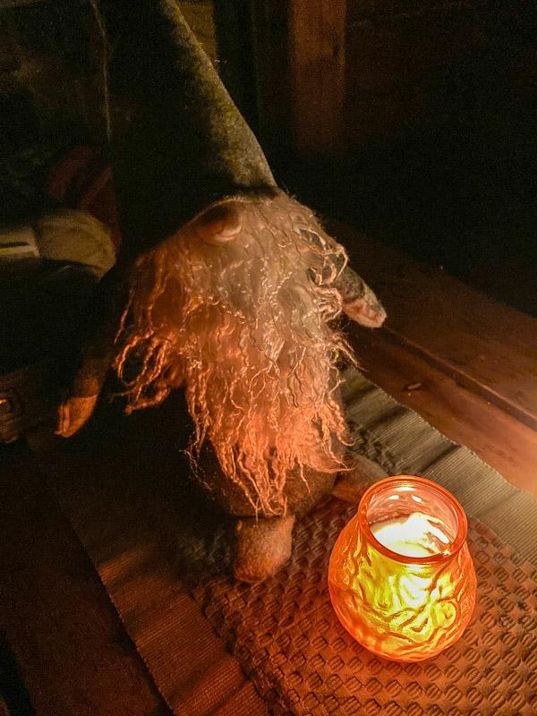Hangasjärven retkikämpän joulusaunan valkopartainen tonttunukke ja kynttilä.