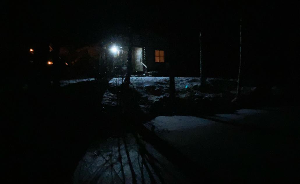 Talvi-illan pimeyden keskellä joulusauna ja puiden varjot lumen peittämällä jäällä.