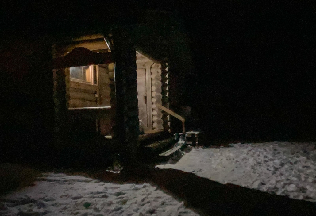Hangasjärven joulusauna ja valaistu kuisti pimeänä talvi-iltana.