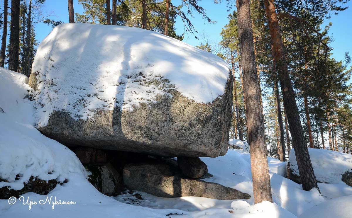 Iso lumen peittämä kivi polun vieressä.