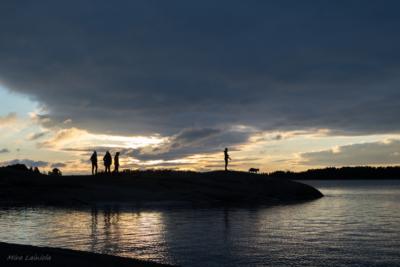 Ihmisiä pimeällä rantakalliolla meren rannalla