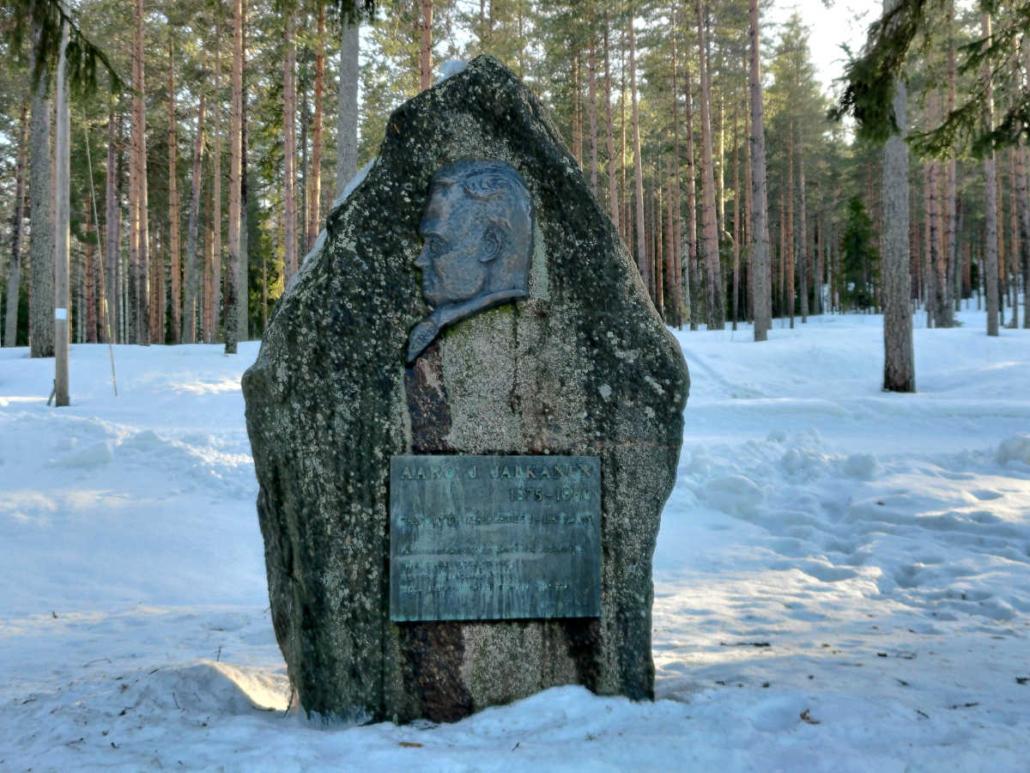 Aaro jalkasen kivinen muistomerkki. Kivessä on miehen profiilikuva ja laatta, jossa on Kallavesj-laulun yhden säkeen sanat kohokirjaimin.