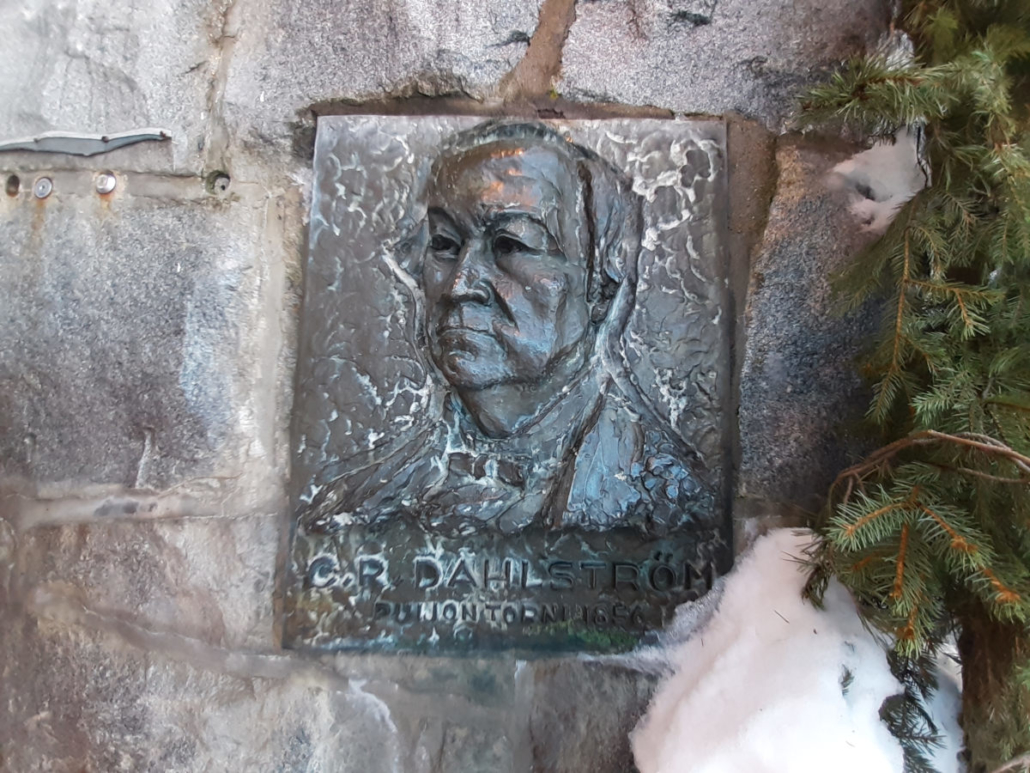 C.R. Dahlströmin, Puijon ensimmäisen tornin rakennuttajan muistolaatta Puijon tornin kivijalassa. Kuvan oikeassa reunassa kuusen oksia ja lunta.