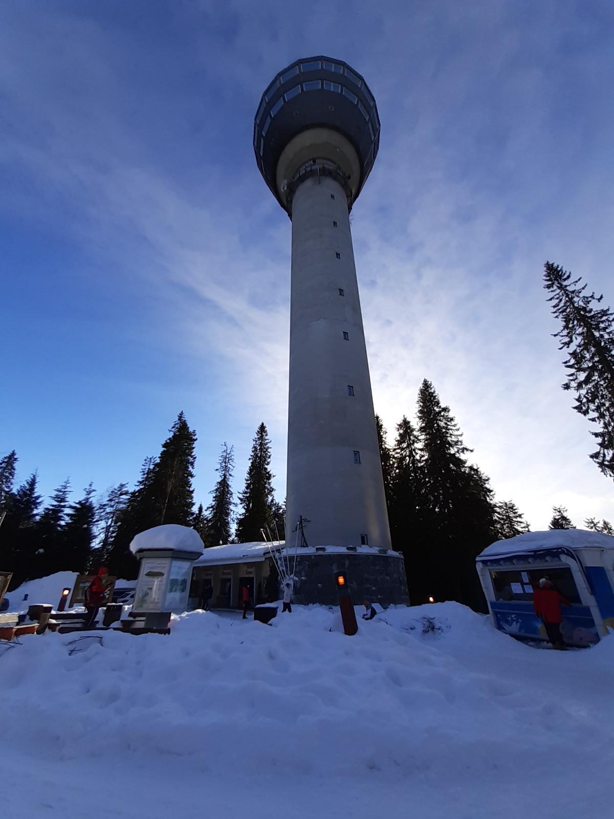 Puijon torni talvella. Ihmisiä ja opastuskoju sekä kioski. Taustalla Puijon kuuset.