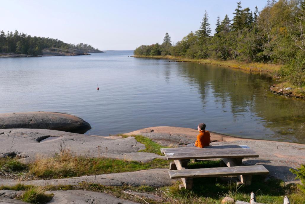 Henkilö istuu pöydän äärellä katsellen maisemaa merelle