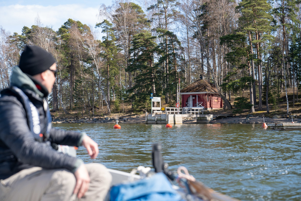 Veneilijä veneessään Malkasaaren sauna näkyy taustalla