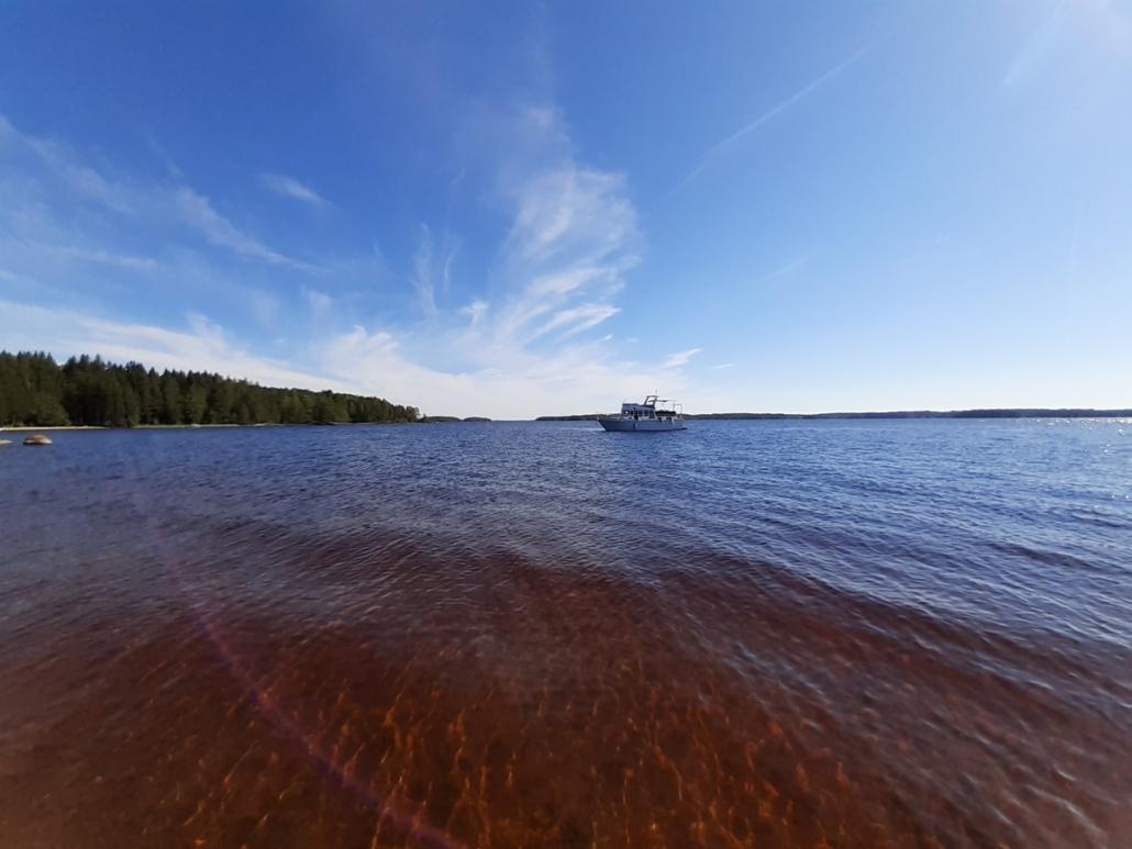 Upea sininen taivas, jossa valkeita pilviä. edessä laiva ja etualalla Hietasalon kaunis hiekkaranta.