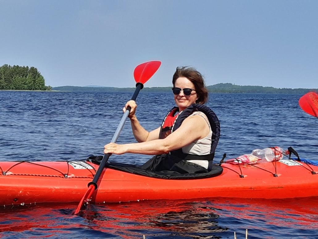 Nainen meloo Kallavedellä punaisella kajakilla. Taustalla vettä ja metsää sekä taivasta.