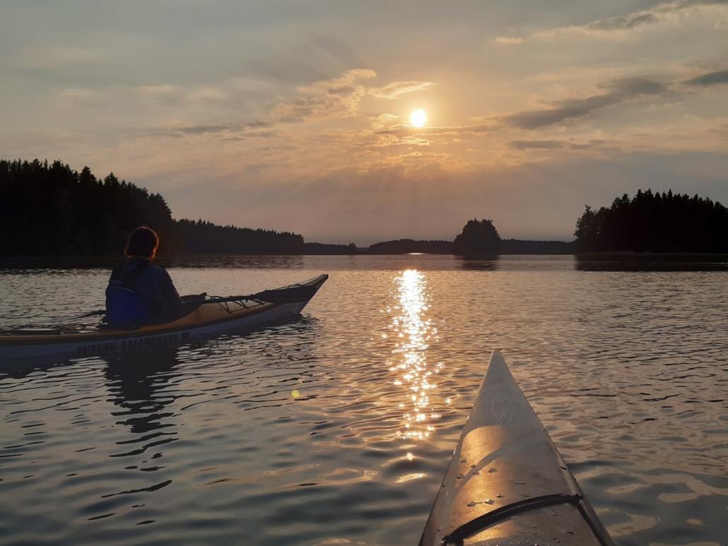 Kajakit etualalla. Aurinko laskee saarten taakse Kallavedellä.