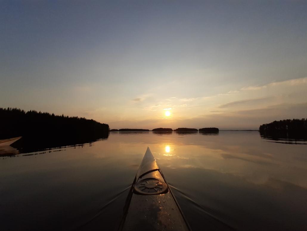 Aurinko laskee Kallavedellä saarten taakse. Kajakkien keulat näkyvät kuvassa.