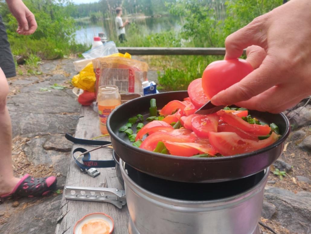 trangia. salaattia trangian kannella. kädet. Kalastaja taustalla.
