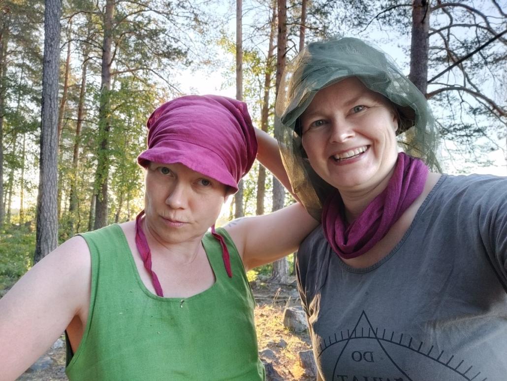 Kaksi naisoletettua poseeraa selfiessä takanaan metsää, jonka takaa tulee valoa.